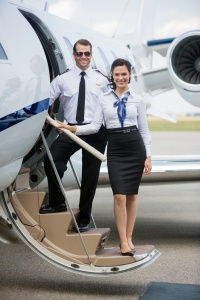 Confident Airhostess And Pilot Standing On Ladder Of Private Jet