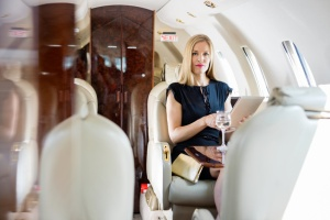 Wealthy Woman Holding Tablet Computer In Private Jet